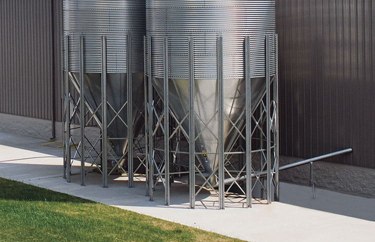 Bulk material storage silo with flexible or solid screw conveyor takeaway